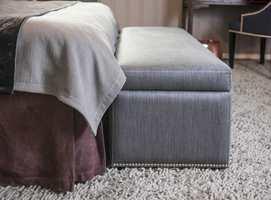 FOTSIDT SKJØRT: Sengeskjørtet i stenvasket lin faller lekkert mot gulvteppet. To sengetepper, det ene i velur, og en puff i et blankere tekstil, er en spennende  miks av teksturer.