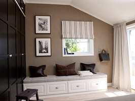 Mørke skap i kontrast til den lyse sittebenken og det lysnede gulvet, og tapet, gardiner og puter binder det hele sammen. Terrassedørene sørger for vakkert lys.