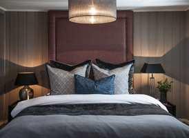 HERSKAPELIG: Blanke og matte tekstiler er blandet. Sengegavlen er selve prikken over i-en, og er strukket til taket for å illudere større takhøyde.