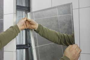 Bruk dobbeltsidig tape ved ettermontering av speil på bad.