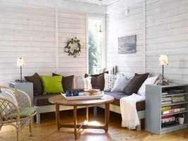 Rommet er ikke til å kjenne igjen! Taket er malt, veggen lysnet med panellakk og den nybygde, blå sofabenken med alle sine puter lager en fin atmosfære. Hyllene rammer inn sofaen.