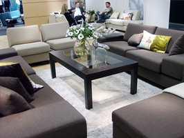 Norske Stordal har tatt frem to nye sofakolleksjoner som de viste frem i Stockholm. Den litt kantete Giske-serien hadde mykt ullstoff fra Innvik Sellgren AS og store firkantete wengebein, som er årets treslagstrend. Til de brede vangene finnes praktiske brett i det samme treslaget. Foto: Chera Westman