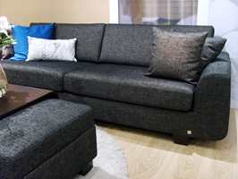 Denne treseters sofaen fra Stordal inngår i den nye serien Ålesund. Lengden er hele 2,5 meter fra vange til vange, og designen organisk rund. Organiske blomstermønstre passer godt på pynteputer og kompletterende møbler, men kan bli for dominerende på en svær sofa. Foto: Chera Westman