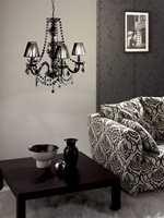 Kandelabere og lysekroner i sort, gjerne med prismer og romantisk barokklignende stil, er i skuddet. Denne er fra Massive. Foto: Produsenten