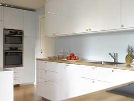 ET ROLIG HJØRNE Avstemt og delikat – denne kjøkkendelen er holdt i fire farger; blågrønne vegger (S 1005-B50G), hvit innredning, messingknotter og benkeplater og gulv i eik.