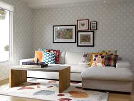 STEMNINGSFULLT Stuen har fått samme tapet på alle veggene. Det geometriske mønsteret er såpass åpent og fargen så dempet at man ikke får opplevelsen av mye mønster. Det skaper tvert imot en fin og rolig bakgrunn for bilder, møbler og tekstiler. Den blågrønne fargen går igjen i alle rom, og tas opp i både teppe og puter, som for øvrig også har farger fra de andre rommene. Ikke minst er det passe mengder av Torhilds favorittfarge – oransje.