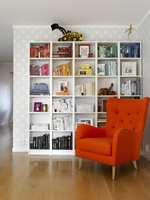 SYSTEM I FARGEGALSKAPEN Selv bokhyllen, med bøkene sortert etter farge, vitner om at det ikke er noen hvem som helst som bor her. Her blir den nærmest som en installasjon å regne, akkompagnert av den varmoransje stolen, og med tapetet som ramme – bokstavelig talt. Løden i gulvet passer fint til omgivelsene. Gravemaskinen, egenhendig bygget av mannen i huset, utgjør et passe rampete innslag!