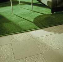 Rutene i flisene gjentas i teppet. Veving med luv i to ulike høyder gir mønsteret