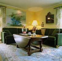 Vnterstue med mørk sofa og tette gardiner.