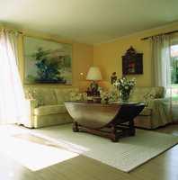 Sommerstue med lys sofa og lette gardiner og lyst teppe.