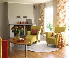 Elipseformet sofabord, rundt teppe og moderne lenestoler med bueformet skammel, myker opp i et kvadratisk rom.