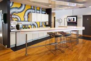 Tekjøkkenet er dekorert med bildetapet med høyst relevant motiv for å markere bedriftens virksomhetsområde. Legg merke til bordet som er formet som logoen - et syvtall.