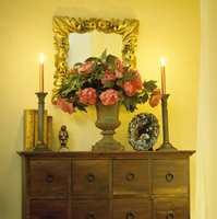 Fete gullrammer og frodige blomsterbuketter skal det være. Klassiske lysestaker i bronse og jernurne er helt i stilen.