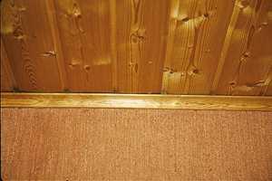 Panelet ble i sin tid behandlet med klar panellakk. Lysfilteret er for lengst brutt ned og treverket har blitt mørkt gulbrunt.