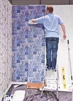 <b>ENKELT:</b> Smør limet på veggen, fest høyden ved taket, stryk ut luftbobler og skjær av nederst ved gulvet.