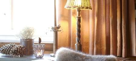 Heng opp tette gardiner mot et blomsterbrett - det er gunstig for strømbruken.