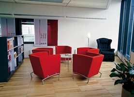 Telenor Fornebu har åpne kontorløsninger, men med sittegrupper og små avlukker for en stille stund eller et lite møte. Fargene i de enkelte fløyer følger nærmest fargesirkelen. Her er vi i den vestlige delen der rødt dominerer i møbler og gardiner.