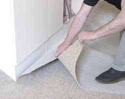 Grovtilpass teppet til gulvet ved å skjære av overflødig teppe. Da blir den lettere å jobbe med. Fintilpassingen gjøres senere.