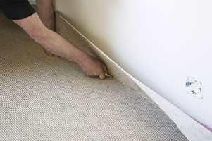 Bruk en skarp kniv og skjær teppet inn mot list/vegg og i hjørnene.