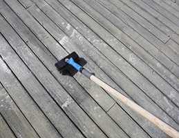 Påføring vått-i-vått av terrasserens med en vaskekost påmontert et forlengerskaft.