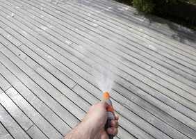 Terrassen spyles så grundig med haveslagen - alt rensemiddel skal bort før sluttbehandlingen.