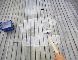 Terrasseoljen påføres feltvis med en malerrull. Deretter brukes en bred beispensel i lange drag for å stryke oljen skikkelig ut og komme mellom bordene.