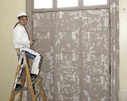 Den gamle hovedinngangen i Skolebygningen. I alle tak er det brukt limfarge. Veggene er malt med linoljemaling; det samme er dører og vinduer. Fremgangsmåten var først å grunne med linolje, flekksparkle og to strøk med linoljemaling på topp.