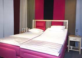Fargerikt og matchende - rosa på både seng og tekstilpanelene. Farger matches.