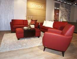 Sterke røde innslag både på tekstiler og skinn på møblene, men parketten, teppet og puter/pledd holdes i helt lyst.
