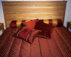 Et gjennomført sammensatt sengesett på soverommet - i de skinnende tekstiler. Sengen er av eik. (Fra CS Möbelfabrik)