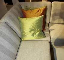 Den skinnende tekstiltrend på putene i kontrast til det dempende grå-grønne møbelstoffet. (Fra Formfin)