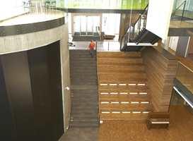 Til venstre betongsylinderen i fellesarealet, som har fått et overflatesjikt uten at det vises, påført en klar base uten tilsetting fordi betongen skal støvbinde og være lett å holde ren. Mosaikkparketten er også brukt som tribuneløsning.