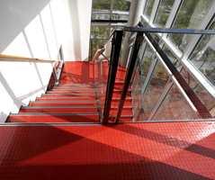 Det er lagt ca. 3.500 m2 gummibelegg - i en grå hovedfarge, men med sterke innslag som rød og grønn i trapperom.