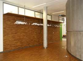 Mosaikkparketten er brukt også på vegg i garderoben, i kontrast til betongsylinderen som går over flere etasjer og inneholder fellesarealer.