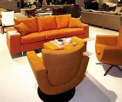 Runde former på stolene, en rett form på sofa - i oransje nyanser og med blomsterdekor på sofaputene. (Fra Brunstad)