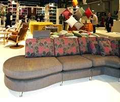 Hybrid møbel - både sofa og seng i en av årets motefarger, bruntoner. Sofaputene har større blomstringer. (Fra Brunstad)