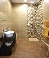 Store fliser på gulv og vegg, kombinert med mosaikkflis i dusjhjørnet, i beige- og bruntoner.