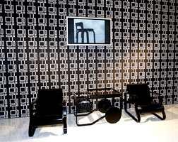 Sorte designmøbler kombinert med retromønster i sort-hvitt og flatskjerm på vegg. (Finsk design)