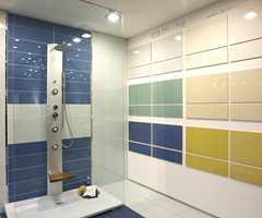 Blått innslag i dusjkabinettet, mens utstillingen på vegg viser matchende flisstørrelser. (Höganäs).