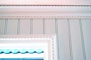 Kombinert løsning både i tak og rundt vinduet. I taket er det montert en skrålist i midten med et såkalt taulistverk både over og under. Taulistverket går igjen ved vinduet, her kombinert med en tynnere dekorlist.