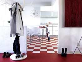Vinylbelegg i moderne design hvor det i kjøkkenet er lagt sjakkmønster i kombinasjonen rød og hvit. Rutemønsteret til tross - dette er en banevare. I entreen er det brukt en alternativ vinyl - i ensfarget rød. (Novilon fra Forbo)