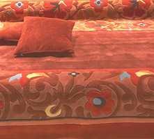 Jordfarger over i rødt - igjen med mønster fra natur og flora. Tekstiler, som her på pute, matcher teppet.