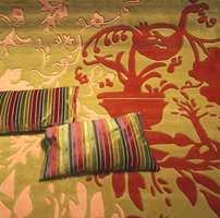 Igjen de kraftige mønstre på teppet i flotte, sammensatte jordfarger, matchende med puter i de like typiske blanke tekstiloverflater. Stripemønster er en gjenganger.