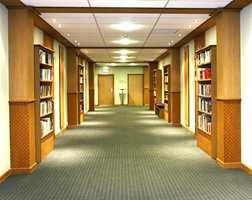 Korridor i møteavdelingen med søyler og bokhyller kledd med glatt eller dekorert finér.