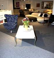 Forretningens øvre plan med kombinasjon av teppefliser i lys grått og mellomgrått.