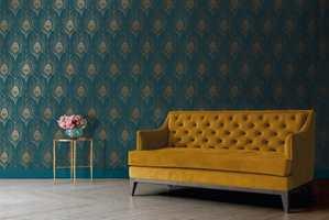 Gul sofa og grønn tapet med påfugelfjær