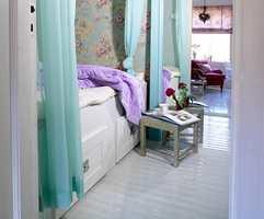 Lys turkisfarge illuderer både frisk luft og lys. Flortynne gardiner gir rommet et svalt inntrykk og skjermer samtidig sengen.
