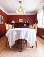 <b>DYP RØD:</b> Spisestuen ble dyp rød, for å skape et brudd i den duse harmonien og for å gi de lyse stolene en fin ramme. Veggene er sjablonmalt av malermester Anne Louise Gjør. Farger: Rød vegg S 3330-Y50R, Tak og vindu S 0502-Y.