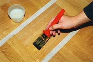 Bruk reparasjonslakk. Påfør et fyldig førstestrøk, deretter 2-3 toppstrøk litt avhengig av hvor dypt ned gulvet er slipt.