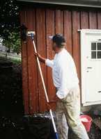 Veggen skal males på nytt, og her brukes et kraftvaskemiddel som gir ekstra god heft til etterfølgende malingstrøk.